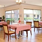 Very clean and nicely lit resident dining area with a view of the outside patio