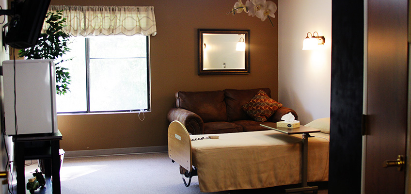 one bed room with a window and couch and television
