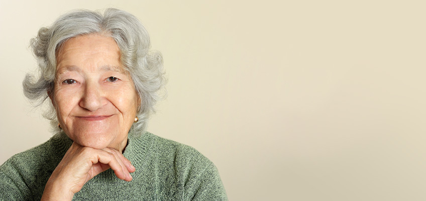 elderly woman smiling with her hand on her chin