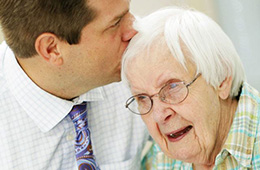 man kissing an older woman on the top of the head