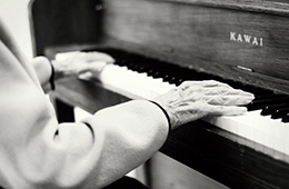 old hands playing on a piano