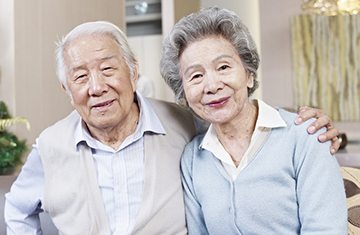 elderly couple, he has his arm around her shoulder and they are smiling