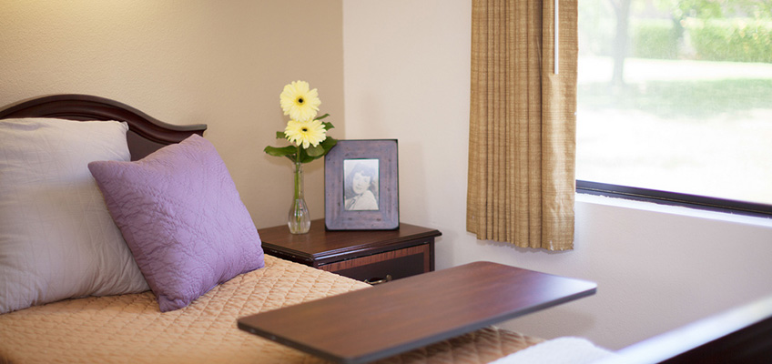 bed with flowers in the side table by the window