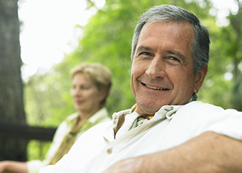 man smiling with woman in the background