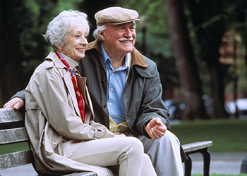 couple seating on a park bench smiling