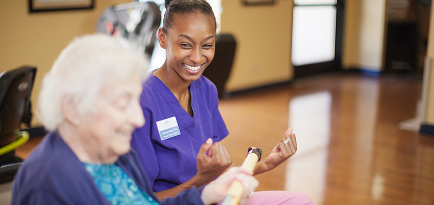 elderly woman and physical therapist smiling and exercising