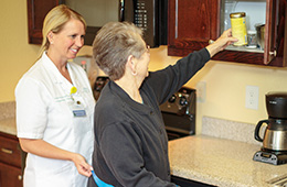 resident reaching for some coffee while a staff member is smiling next to her