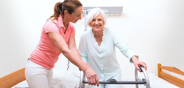 Rehabilitation staff working with a resident using her walker