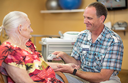 resident receiving therapy from smiling male attendant