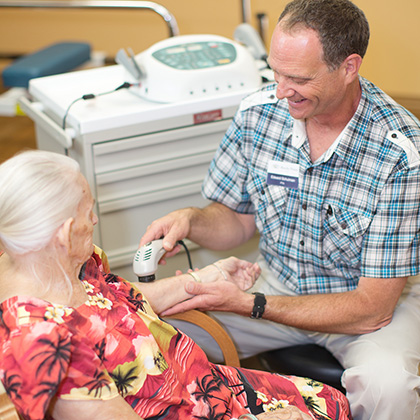technician administering therapy to resident's arm