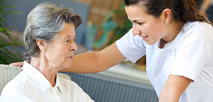 A nurse leaning in toward a resident she is assisting