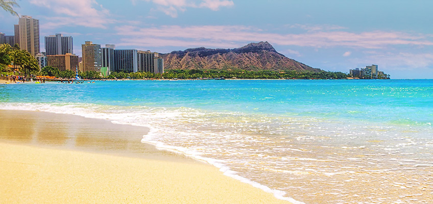 Oahu beach with the mountains and large sky rise buildings in the background