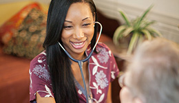 smiling nurse with stethoscope taking vitals