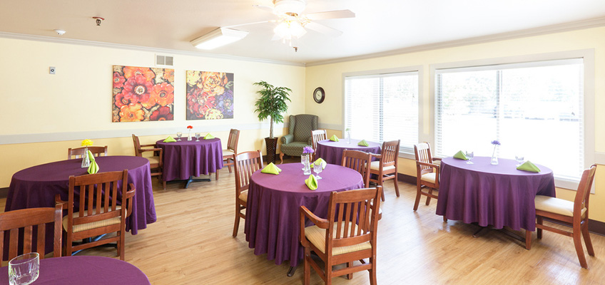 dining room with tablecloths, artwork and natural light