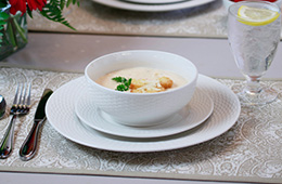 a cream based soup with croutons and parsley on a dining table