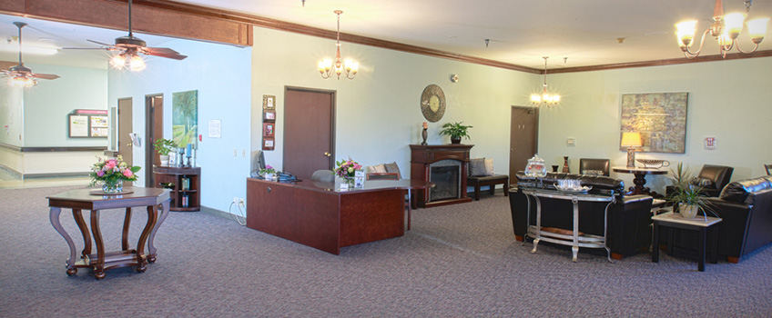 lobby area with fireplace and desks and chandliers