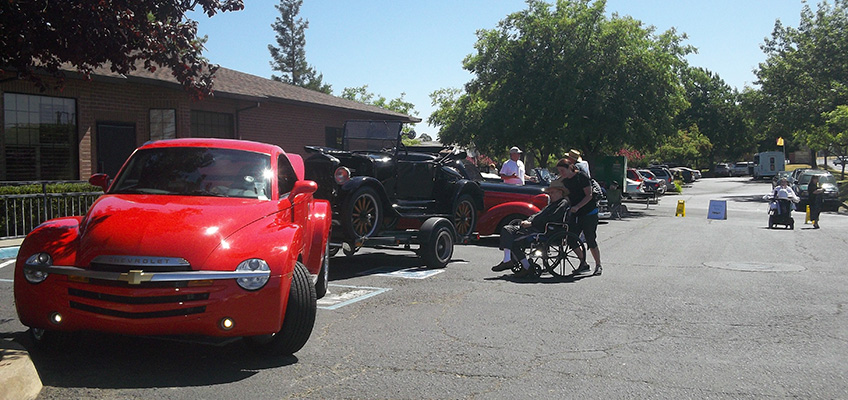 a row of classic cars with residents viewing them