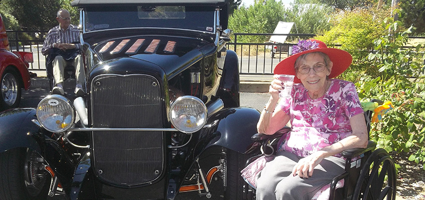 woman sitting in a wheelchair drinking water next to a classic car