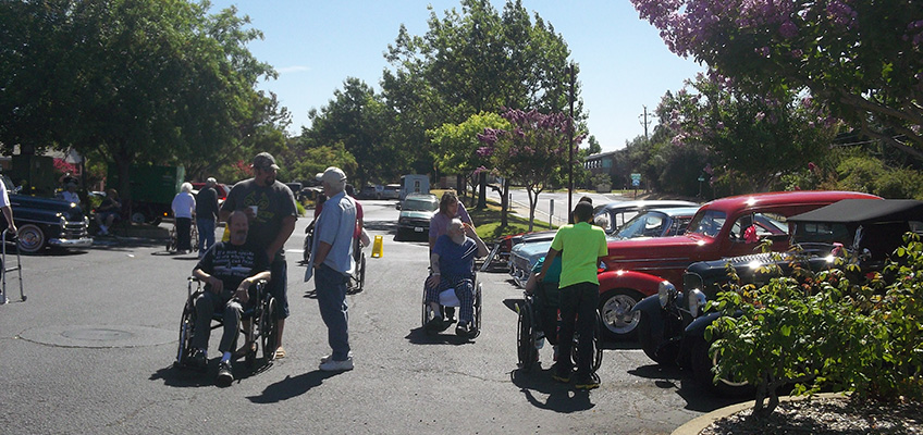 many people in wheelchairs looking at nice antique cars