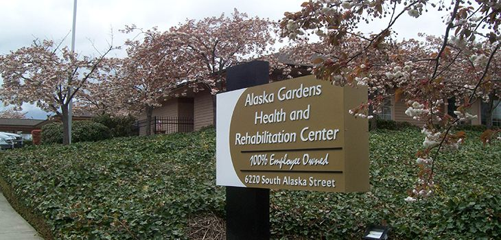 Alaska Gardens Health and Rehabilitation Center sign surrounded by greenery and lush trees