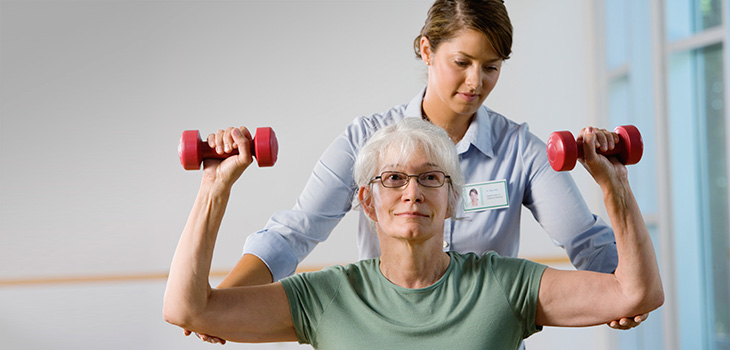 woman using small hand weights while working with a physical therapist