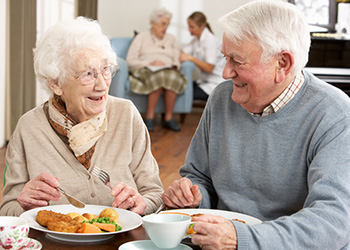 smiling elderly couple eating