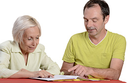 man helping his mother sign papers