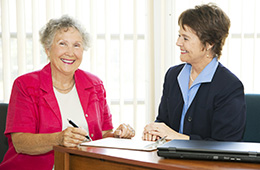 two women sitting and signing documents