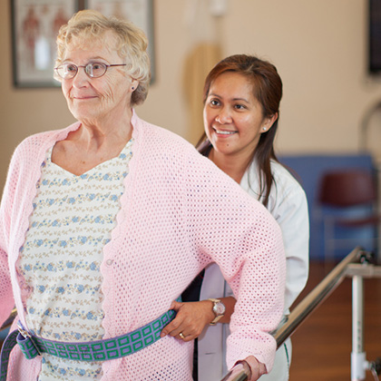 Nurse assisting resident on rehab equipment