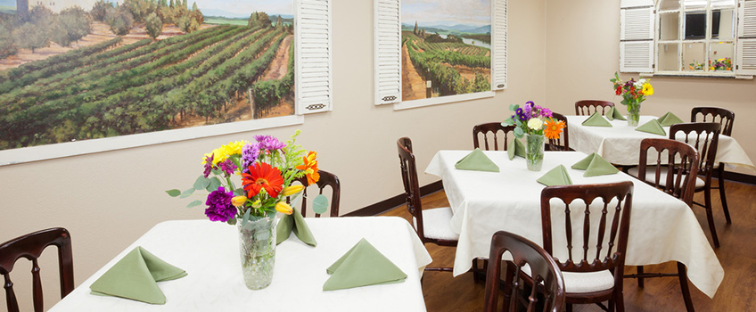resident dining area with decorative napkins set and flowers on each table