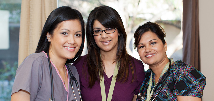 three staff members smiling together