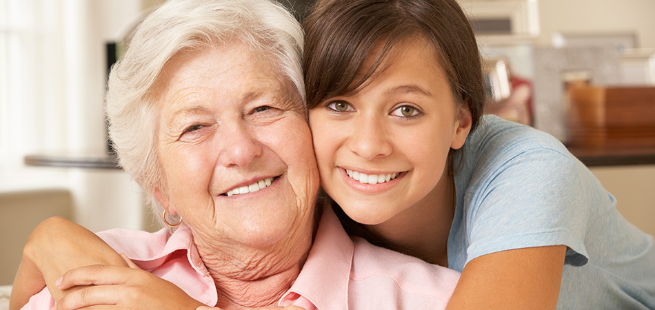 A grandmother and granddaughter smiling together