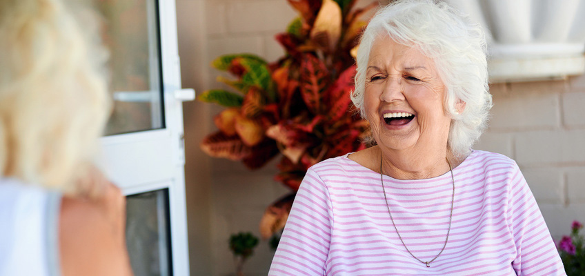 Elderly woman laughing outside