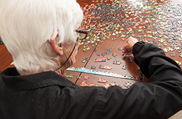 Elderly woman sitting down doing a puzzle with several small pieces