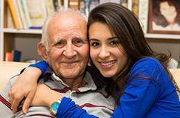 smiling elderly man sitting with daughter