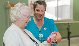 Rehabilitation staff member assisting a resident with dumbell exercises