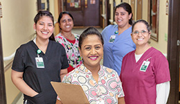 Staff members in the hallway together smiling with resident rooms behind them