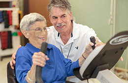Rehabilitation team member assisting a resident on an exercise bike in the rehab room