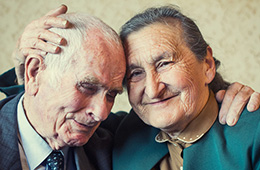 an elderly couple embracing while smiling