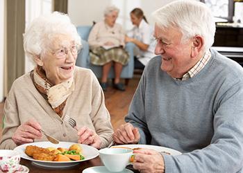 smiling elderly couple eating