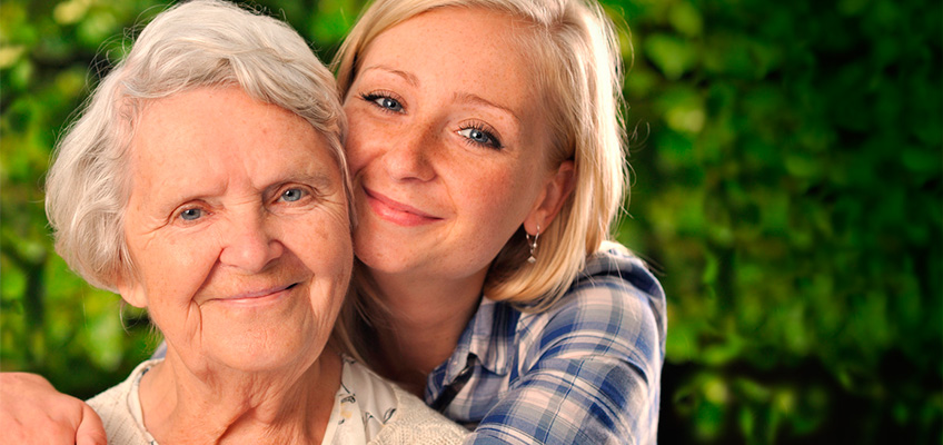 grandmother and grandaughter smiling and hugging with green plants in the background
