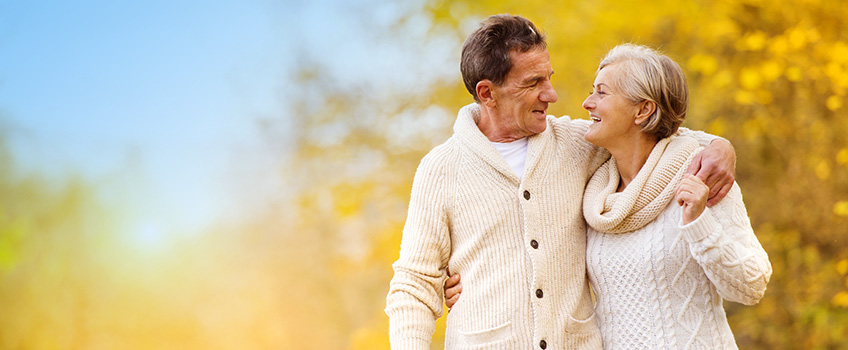 smiling couple wearing textured wool sweaters in an autumn background
