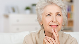elderly woman sitting and thinking with her hand on her chin