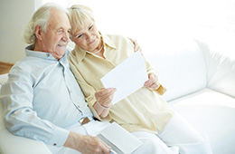 elderly couple reading mail