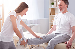 female physical therapist helping a man stretch out his knee