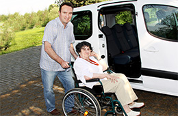 man helping a lady in a wheelchair into a van