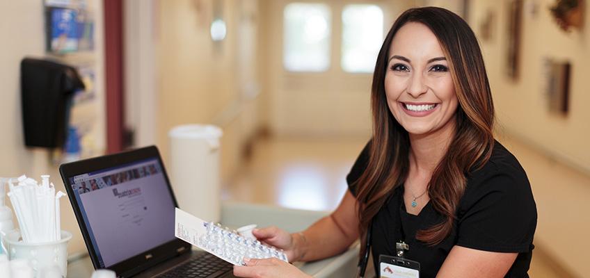 smiling nurse working at laptop