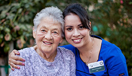 nurse smiling with her arm around resident
