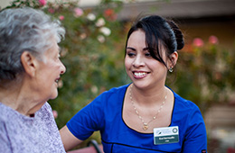 nurse smiling at resident outdoors with flowers in the background