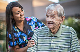 nurse outside smiling with resident